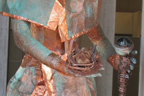 OBJECTS of curiosity held by the Bronze Queen sculpture in downtown Boston Park (In close up)